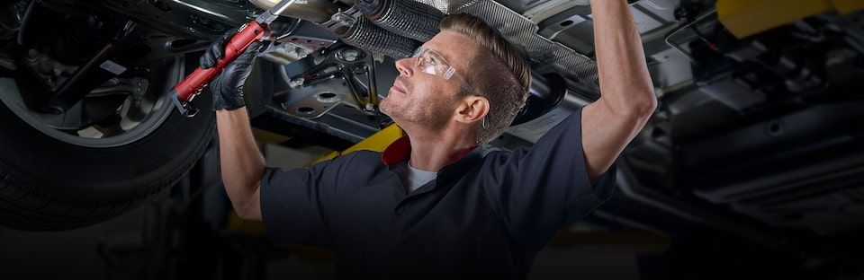 Cadillac Certified Service technician working on the underside of a vehicle