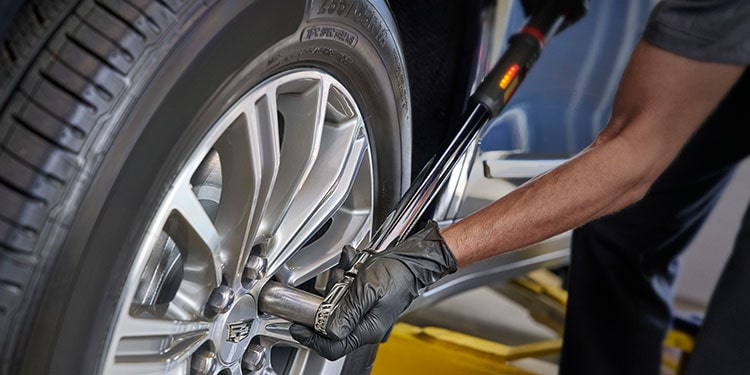 Cadillac Certified Service Technician Changing Vehicle's Tire