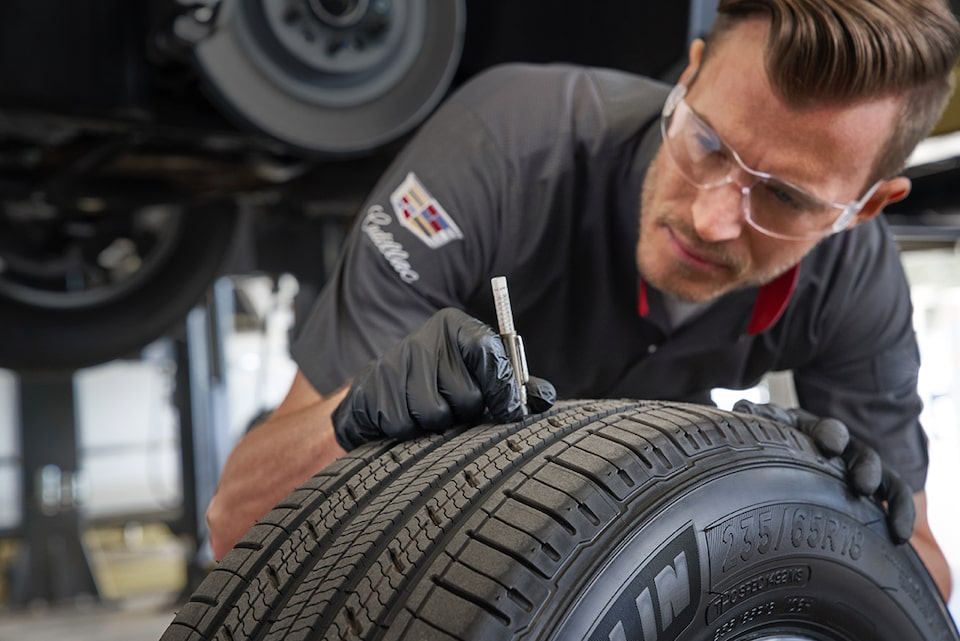 Cadillac Protection Expert Checking Tire