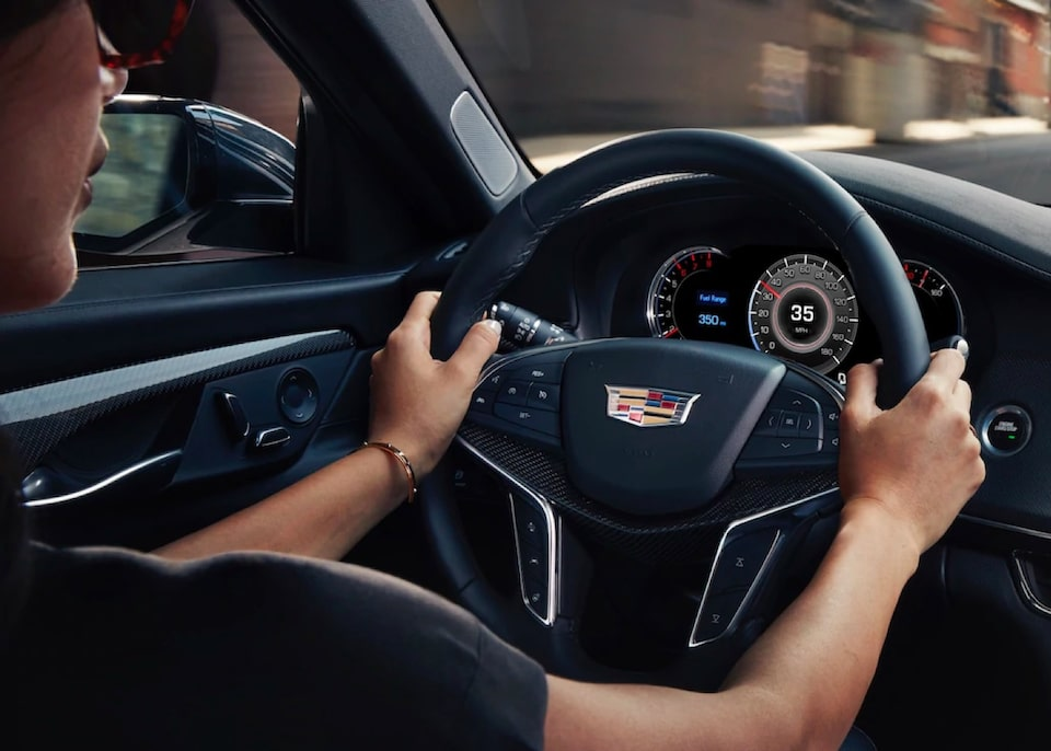 Cadillac First Responders Discount Program: A person hands on the Cadillac steering wheel