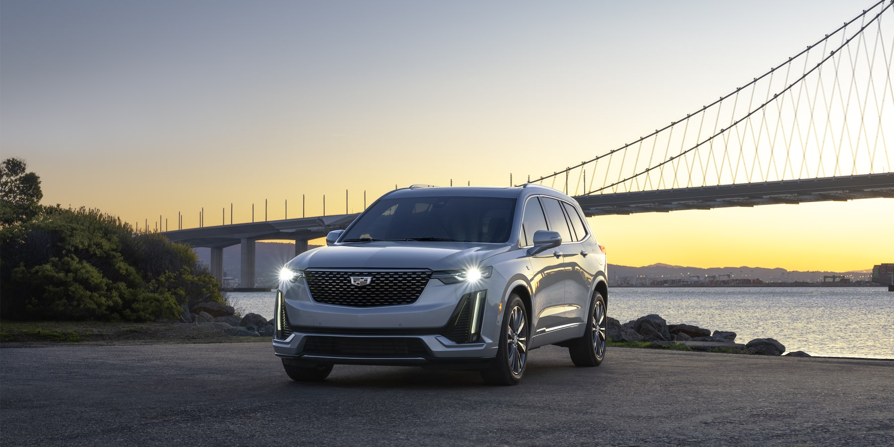 2021 Cadillac XT6 parked in front of a body of water and bridge